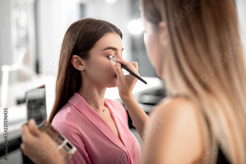 Leinwanddruck Bild Visagiste holding palette with shadows while making make-up for pretty lady with special brush