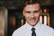 Concept of success and confidence. Close up portrait of handsome smiling successful male looking straight on camera