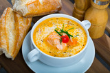 Delicious soup with salmon, served  in bowl with fresh bread at table