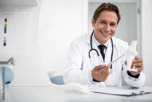 Emotional cheerful doctor in white uniform kindly smiling and demonstrating the knee model