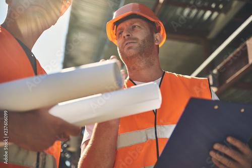 Doświadczony budowniczy w pomarańczowym kasku stojący obok kolegi i przytrzymujący schowka podczas rozmowy z nim