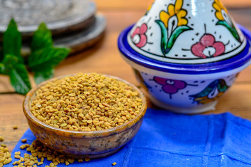 Bowl with fenugreek seeds close up, used for cooking and traditinal medicine, spices collection