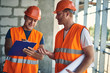 Enthusiastic builder holding clipboard and smiling while making notes and talking to colleague