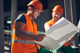 Positive emotional builder in orange vest and helmet smiling happily while sitting with his colleague and looking at the drawing - 237607426
