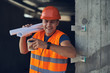 Positive emotional builder in bright orange uniform standing next to the wall and smiling while holding carton cup of coffee and drawings