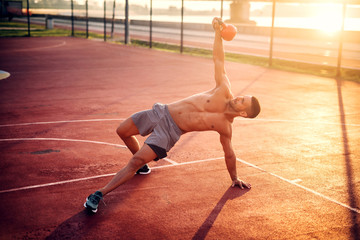 Handsome man working exercises in early morning with sunrise. Fitness training outdoors.