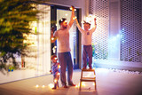 happy family, father with sons decorate open space patio area with christmas garlands - 237620254