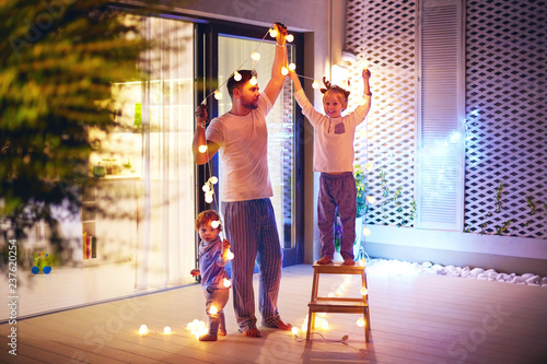 Leinwandbild Motiv happy family, father with sons decorate open space patio area with christmas garlands