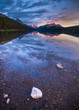 Sun sets over distant snow capped mountains overlooking a beautiful alpine lake