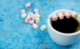 white cup of coffee and marshmallows on the table. vertical view. place for text. Abstract blue background.