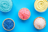 Spa salt background. Colorful spa salt in bowls on blue background top view. Yellow, turquoise, pink, purple spa salt