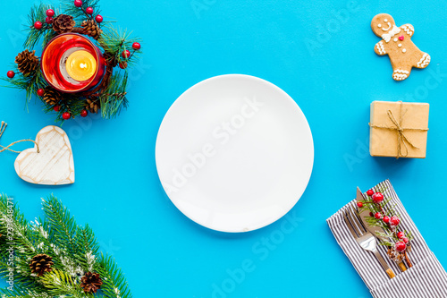 Christmas dinner decoration with gift box, plate and fir tree blue table background top view mock-up - 237648471