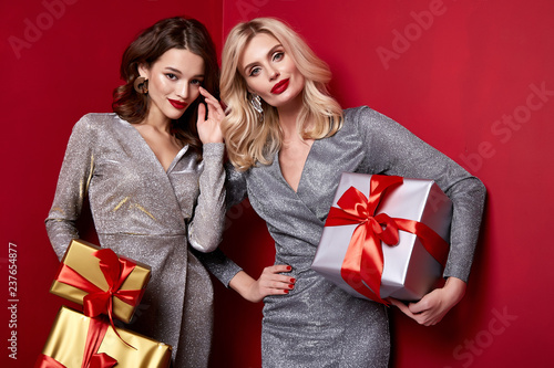 Two beautiful sexy young woman bright evening make-up red lips long fluffy eyelashes hold gift box holiday New Year  joy fun happy merry Christmas Eve party celebration St. Valentine's Day girlfriend. - 237654877
