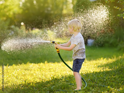 Leinwanddruck Bild Funny little boy playing with garden hose in sunny backyard. Preschooler child having fun with spray of water.