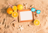 Wooden frame, glass of orange juice, sunglasses and seashells on sand beach. Top view, copy space.