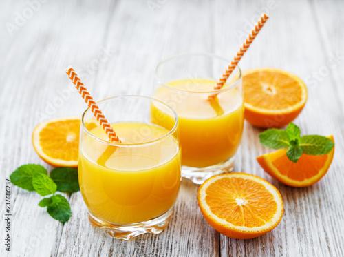 Szklanki soku i pomarańczowe owoce