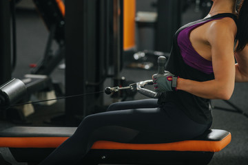 Side view of woman doing exercises with rowing machine at gym.