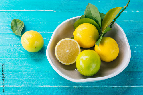 Lemon in a plate on a turquoise wooden background, citrus, vitamin C