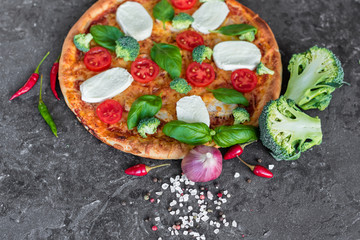 Pizza, food, vegetable, margarita. Vegetables, mushrooms and tomatoes pizza on a black wooden background. It can be used as a background