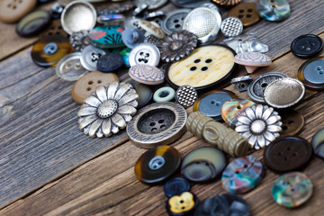 Vintage buttons in large numbers scattered on aged wooden boards