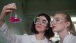 Chemical laboratory. Two young women looking at the flask with pink liquid
