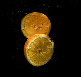 slices of oranges on a black background in water splashes