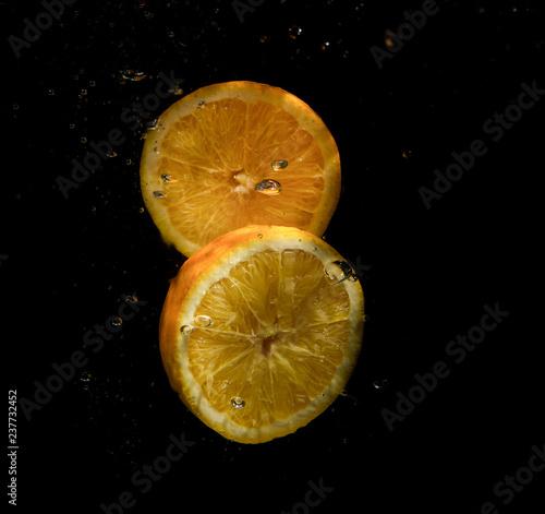 plasterki pomarańczy na czarnym tle w rozprysków wody
