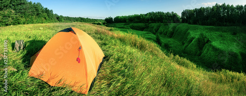 Orange tent on a green hill above a ravine - 237733490