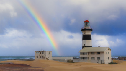 Rainbow in the sky and lighthouse on the sandy shore in the foreground