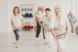 Smiling senior woman with towel exercising during yoga classes for elderly people - 237744457