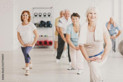 Fototapeta Smiling senior woman with towel exercising during yoga classes for elderly people