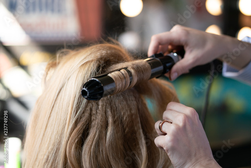 beautiful adult blonde client sits in a chair while a hairdresser master in the salon does her hair with a corrugation and a Perm