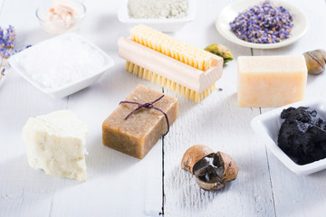 spa products: black mud and clay powder, cosmetic cream, soap, bath salt, shea butter and lavenders on white wood table background © tstock