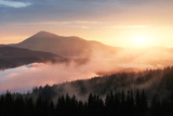 Beautiful sunset in the mountains. Landscape with sun light shining through orange clouds and fog - 237754044