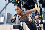 close up view of attractive asian girl in sportswear training with resistance bands in sports center