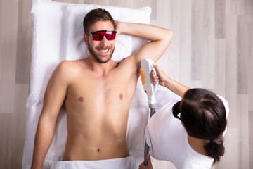 Young Man Having Underarm Laser Hair Removal Treatment © Andrey Popov