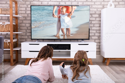 Mother And Daughter Watching Television - 237783626