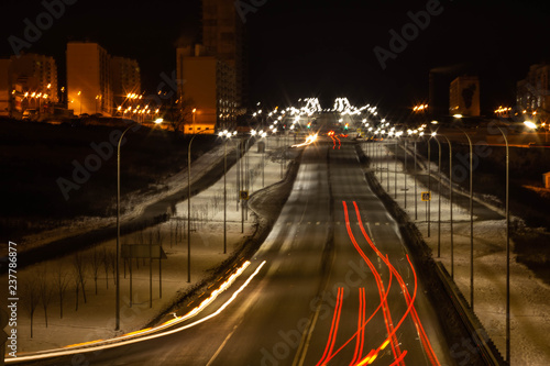 The lights of the cars on the Avenue Aigi in Cheboksary in Russia in the winter evening - 237786877