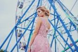 Young beautiful woman in long pink evening dress walking path in park. Fashion style portrait of gorgeous beautiful girl outdoors