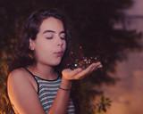 Menina assoprando glitter