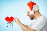 Man in santa hat holds shopping cart with heart. - 237796066