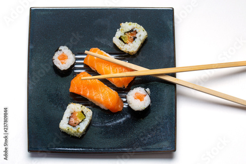 Black plate with sushi, maki, american rolls and chopsticks