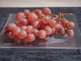 A brush of pink grapes on a decorative plate that occupies the entire plan. Shot from the side.