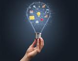Hand holding light bulb on dark background. New apps concept - 237827285