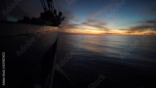 view the side of a boat when it's cruising through a galssy water surface in the sunset. shot with Sony A7S