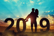 Silhouette of a man holding a woman in his arms while celebrating a New Year 2019.