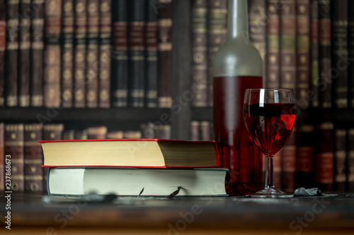 in a room full of books, on the table stands a glass and a bottle of red wine, next to them lies two books