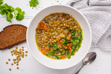 Homemade vegan lentil soup with vegetables, bread and cilantro, white wooden background.