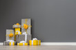 Quadro A pile of yellow and grey Christmas gifts with ribbons against the wall on a beautiful hardwood floor with copyspace
