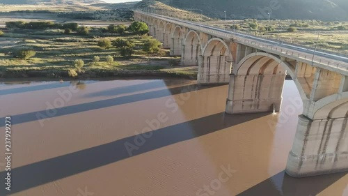 Fototapeta Low Fly Past Arched Bridge over River in Africa